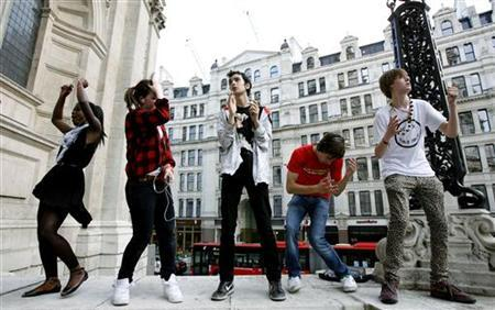 People dance in front of St. Paul's Cathedral as they listen to their personal stereos during a 'mobile clubbing' meeting in London July 19, 2007. REUTERS/Alessia Pierdomenico