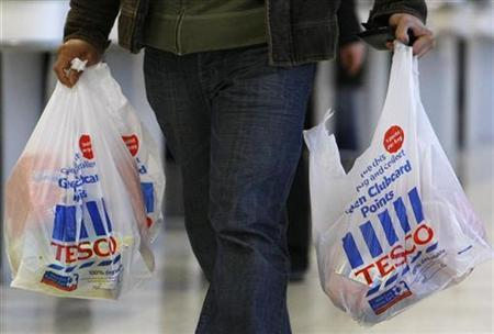 A shopper carries his bags from the checkout as he leaves the Tesco store in Gorton, Manchester, northern England, January 13, 2009. REUTERS/Phil Noble