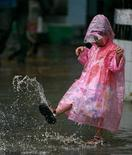 <p>Una bimba gioca in mezzo all'acqua dopo un nubifragio. REUTERS/Arko Datta</p>