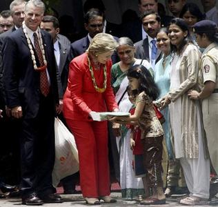 U.S. Secretary of State Hillary Clinton (C) presents a gift to a child during her visit to Sewa, a women's self employment voluntary organisation, in Mumbai July 18, 2009. REUTERS/Stringer