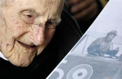 <p>World War One veteran Henry Allingham looks at a card displaying a picture of a World War One pilot during his 113th birthday party at HMS President in London in this June 6, 2009 file photo. REUTERS/Luke MacGregor/Files</p>