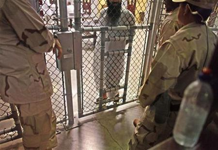 In this photo, reviewed by the U.S. military, a Guantanamo detainee speaks with guards inside the Camp 6 detention facility at Guantanamo Bay U.S. Naval Base in Cuba, May 31, 2009. REUTERS/Brennan Linsley/Pool
