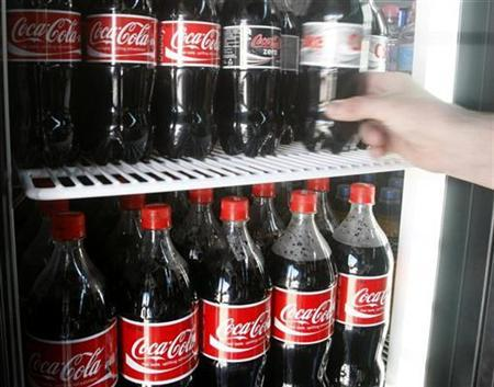 A customer takes a bottle of Coca-Cola from a grocery store fridge in Melbourne, November 17, 2008. REUTERS/Mick Tsikas