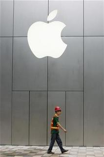 A worker walks past Apple Store at The Village, Sanlitun in Beijing, July 29, 2008. REUTERS/Claro Cortes IV