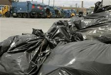 <p>A mound of garbage bags sit in front of a row of garbage trucks parked at the Ingram transfer station in Toronto July 13, 2009. REUTERS/Mike Cassese</p>