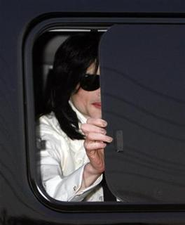 Michael Jackson opens a car window to greet fans as he arrives at the venue for the ''Premium VIP Party with Michael Jackson'' in Tokyo March 8, 2007. REUTERS/Kiyoshi Ota