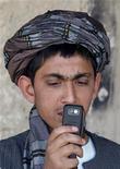 <p>Un ragazzino afghano registra un video sul suo cellulare mentre alcuni soldati canadesi pattugliano il suo negozio a Kandahar, qualche mese fa. REUTERS/Jorge Silva</p>