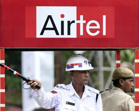 A traffic policeman directs traffic under an advisement of Bharti Airtel at a booth in Ahmedabad July 31, 2009. REUTERS/Amit Dave