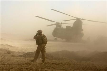 A U.S. Marine talks on his radio while a Chinook helicopter carrying British soldiers from B Company, 2 Mercian, prepares to take off in Malgir, Helmand province July 27, 2009. REUTERS/Omar Sobhani