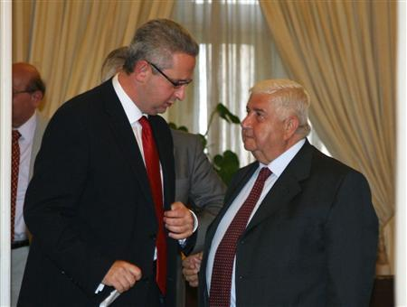Syria's Foreign Minister Walid al-Moualem (R) chats with British Foreign Office Minister Ivan Lewis after a meeting in Damascus August 4, 2009. REUTERS/Khaled al-Hariri