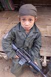 <p>Myanmar, un bambino-soldato di 12 arruolato nelle milizie ribelli Karen. La foto è del 31 gennaio 2000. REUTERS/Jason Reed</p>