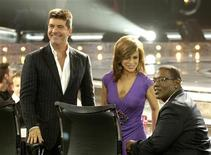 "<p>Judges Simon Cowell, Paula Abdul and Randy Jackson look towards the audience between taping at the finale of Fox's ""American Idol"" at the Kodak Theatre in Hollywood, May 25, 2005. REUTERS/Chris Pizzello</p>"