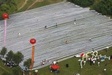 <p>Vista aérea del velo de 2 kilómetros de largo del vestido de una novia en Jilin, China, 6 ago 2009. Una novia china espera ingresar a los libros de récords tras casarse con un vestido con una cola de más de 2 kilómetros de largo. REUTERS/Stringer</p>