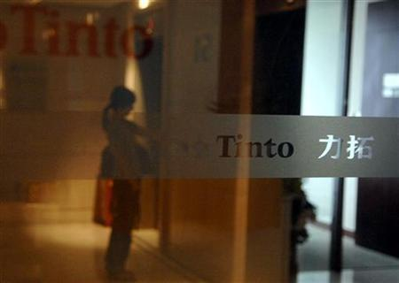 A woman is reflected in a glass door of the Rio Tinto Limited Shanghai Representative Office August 9, 2009. REUTERS/Stringer