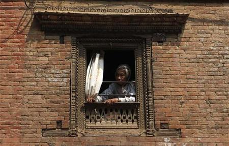 A woman sits inside her house in Kathmandu March 19, 2009. REUTERS/Chaiwat Subprasom