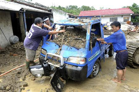 People clean up a pickup truck after Typhoon Morakot swept in Tainan county, southern Taiwan August 11, 2009. REUTERS/Stringer