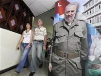 <p>Unas personas caminan frente a una imagen del ex presidente cubano Fidel Castro en un edificio gubernamental en La Habana, 12 ago 2009. Castro fue homenajeado el miércoles con una muestra de 83 fotografías y pinturas, la misma cantidad de años que el convaleciente líder cubano cumplirá el jueves. REUTERS/Enrique De La Osa</p>