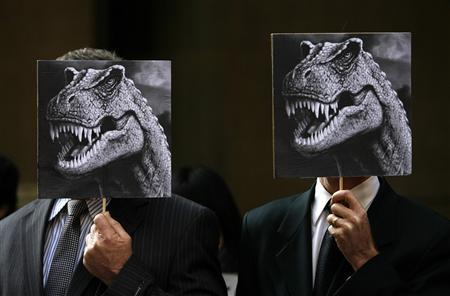 Two men in suits hold pictures of dinosaurs during a protest on climate change in central Sydney August 13, 2009. Australia's parliament rejected on Thursday a government plan for the world's most ambitions emissions trade regime, bringing the nation closer to a snap election. REUTERS/Daniel Munoz