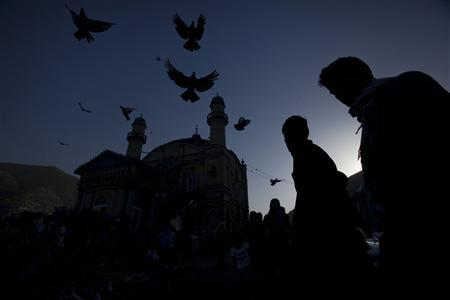 Men stand outside the Shah-Do Shamshira Mosque as pigeons fly over in Afghanistan's capital Kabul August 12, 2009. REUTERS/Adrees Latif