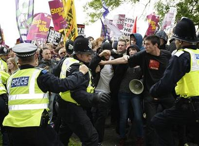 Police officers scuffle with protestors demonstrating against the British National Party's Red, White and Blue event in Denby, central England August 15, 2009. REUTERS/Darren Staples