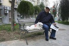 <p>Un cinese seduto su una panchina con il proprio cane in un parco nel centro di Pechino. REUTERS/Gil Murdoch</p>
