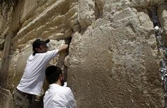 <p>Алан Нир (слева) кладет скрученные послания Богу в расщелины Стены плача, Иерусалим 4 августа 2009 года. Хотите отправить сообщение Богу? REUTERS/Baz Ratner</p>