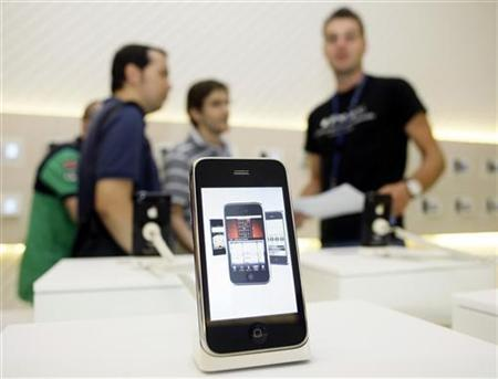 Customers take a look at the new iPhone 3GS on the first day it is being sold in Spain at a Telefonica store in Madrid, June 19, 2009. REUTERS/Susana Vera