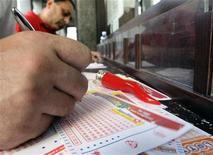 <p>Immagine d'archivio di un giocatore che compila una scheda del Superenalotto. REUTERS/Stefano Rellandini (ITALY SOCIETY)</p>