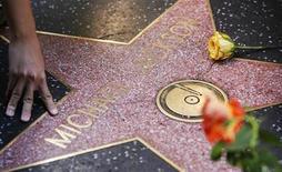 <p>Un admirador posa al lado de la estrella del fallecido cantante de pop Michael Jackson en el Camino de la Fama de Hollywood, 14 jul 2009. El entierro del cantante Michael Jackson fue pospuesto hasta el 3 de septiembre, desde el 29 de agosto previsto, dijeron el viernes representantes de la familia, sin especificar la razón para el cambio. REUTERS/Mario Anzuoni</p>