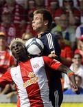 <p>O jogador no Mainz Aristide Bance, que é de Burkina Faso, disputa a bola com Holger Badstuber do Bayern Munich. REUTERS/Thomas Bohlen</p>