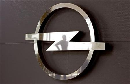 The silhouette of an employee is reflected by the Opel logo at a plant in Antwerp August 21, 2009. REUTERS/Sebastien Pirlet