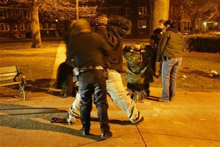 Camden police department officers search suspects in a night raid in Camden, New Jersey, March 24, 2005. REUTERS/Shannon Stapleton