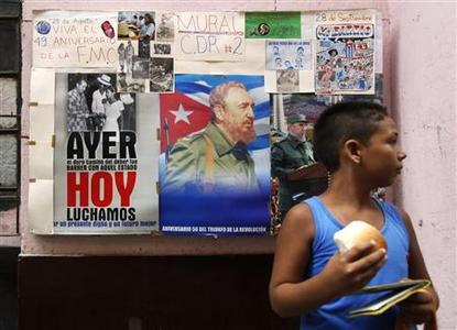 A boy stands by a local neighbourhood revolution defence committee mural in Havana on August 24, 2009. REUTERS/Desmond Boylan