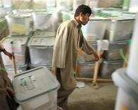 <p>Afghan men transport a ballot box at the Independent Election Commission in Kabul on August 25, 2009. Afghan election authorities were preparing on Tuesday to publish the first partial results from last week's presidential election, but the tiny sample may do little to resolve a dispute over the outcome. REUTERS/Goran Tomasevic</p>