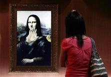 """<p>Una visitante observa una versión tridimensional del retrato de Mona Lisa en Pekín, 21 ago 2009. Por siglos, la """"Mona Lisa"""" de Leonardo da Vinci y su enigmática sonrisa han inspirado tanto especulaciones como admiración. Ahora ella está lista para responder las preguntas, aunque en mandarín. Una versión digital e interactiva de la reconocida pintura del siglo XVI es una de las 61 réplicas de alta tecnología que dan vida a obras clásicas y de la antigüedad en la """"Exhibición Interactiva de Clásicos del Arte Mundial"""" que abrió sus puertas la semana pasada en Pekín. REUTERS/David Gray (IMAGENES DEL DIA)</p>"""