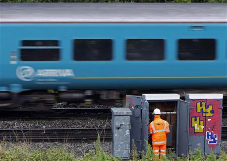 A worker for Network Rail carries out maintenance work by as an Arriva train passes him in Birmingham, August 26, 2009. REUTERS/Darren Staples