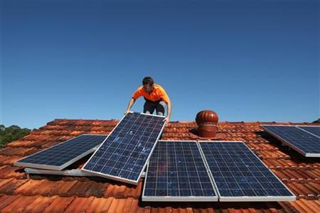 Solar system installer Thomas Bywater adjusts new solar panels on the roof of a house in Sydney August 19, 2009. REUTERS/Tim Wimborne