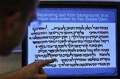 <p>Itay Bar-Yosef, a researcher from Ben-Gurion University, points to a passage of ancient text that a new computer program could help decipher at his office in the southern city of Beersheba August 24, 2009. REUTERS/Amir Cohen</p>