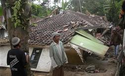 <p>Люди стоят у разрушенного дома в Тасикмалайе, на западе острова Ява 2 сентября 2009 года. Как минимум 15 человек погибли в результате мощного землетрясения на острове Ява, сообщило агентство по чрезвычайным ситуациям Индонезии. REUTERS/Stringer</p>