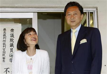 Yukio Hatoyama and his wife Miyuki pose for the media after casting their absentee ballots for the upcoming house election at a polling station in Tokyo August 26, 2009. REUTERS/Kim Kyung-Hoon