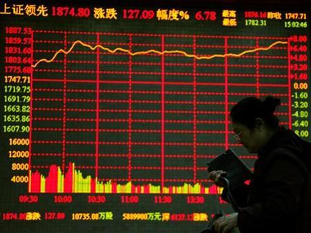 An investor passes in front of an electronic board showing stock information as she leaves a brokerage house at the end of the day's trading in the financial district of Beijing, November 10, 2008. REUTERS/David Gray