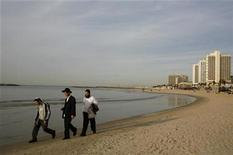 <p>Ultra-Orthodox Jews walk on the beach in Tel Aviv January 14, 2009. REUTERS/Sharon Perry</p>