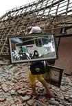 <p>Una donna davanti alle macerie di una casa distrutta dal terremoto a Pangalengan, Giava Ovest. REUTERS/Supri</p>