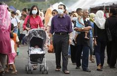 <p>Wearing face masks as a precaution against the H1N1 flu virus, Aszmy Mohamed and his wife Miriza Maarof push their 2 1/2-month-old son Amsyar Aszmy on a stroller as they shop at a Ramadan bazaar in Putrajaya outside Kuala Lumpur, September 7, 2009. REUTERS/Bazuki Muhammad</p>