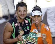 <p>Model Katie Price and singer Peter Andre hold up their medals after finishing the 2009 London Marathon April 26, 2009. REUTERS/Stefan Wermuth</p>