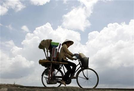 A vendor rides a bicycle on a highway outside Hanoi August 5, 2007. REUTERS/Kham