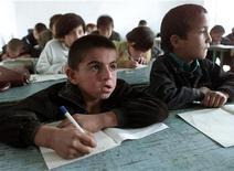 <p>Таджикские дети на уроке в сельской школе недалеко от Душанбе 23 октября 2001 года. В Таджикистане к армии одинаково одетых студентов и школьников добавятся единообразно одетые преподаватели. По приказу министерства образования модельеры уже работают над дресс-кодом учителей. REUTERS/Alexander Demianchuk</p>