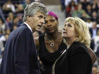 Serena Williams (C) of the U.S. talks with tournament referee Brian Earley (L) and an official during her semi-final match against Kim Clijsters of Belgium at the U.S. Open tennis tournament in New York, September 12, 2009. REUTERS/Andrew Schwartz