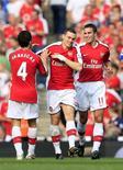 <p>O zagueiro Thomas Vermaelen (centro) comemora com seus colegas seu gol de abertura para o Arsenal. REUTERS/Jed Leicester</p>