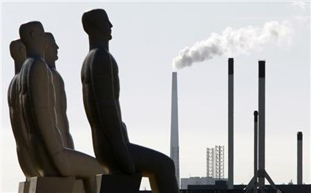 The monument ''The Men at Sea'' by Danish designer Svend Wiig Hansen Esbjerg stands on the coastline as smoke billows from a chimney in the background near Esbjerg in western Denmark September 16, 2009. REUTERS/Bob Strong